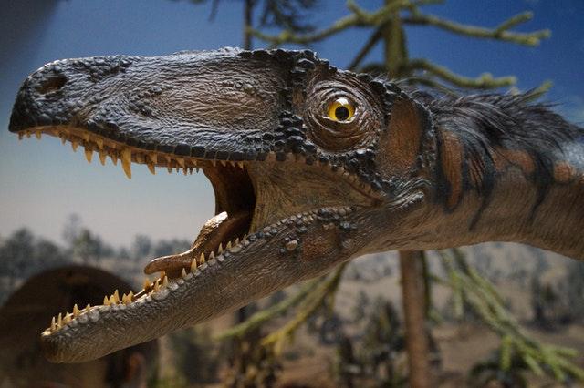brown-dinosaur-beside-green-tree-161959.jpg